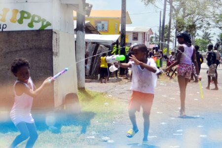 Children playing Phagwah with water guns at Cactus Road, West Ruimveldt