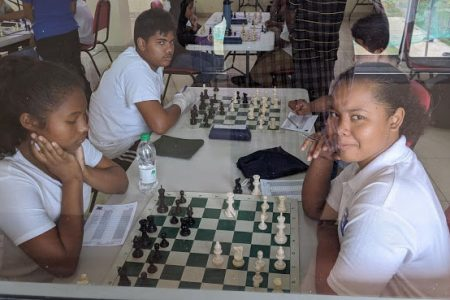 Gyllisa Hamilton (left) of St Joseph High School and Alexia McAdam of Marian Academy, contesting their 4th round game in the Under-16 Development Chess Tournament at the National Stadium, Providence. The tournament has since been postponed to a date to be announced. Before the postponement,  McAdam was in fourth place with three points,  one point behind the leaders. (Photo by John Lee)