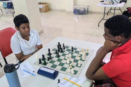 Ronan Lee (left) vs Emmanuel Primus. Lee has scored the maximum four points from the four rounds which he contested in the Under-16 Development Chess Tournament currently being played at the National Stadium. Lee is a student of Marian Academy while Primus attends the School of the Nations. (Photo by John Lee)
