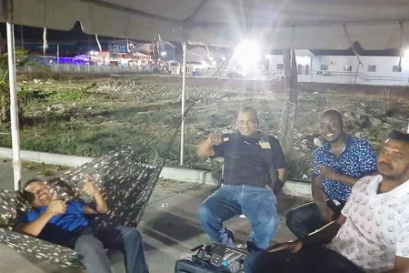 Liberty and Justice Party Leader Lenox Shuman (left) in his hammock accompanied by other party representatives at the Arthur Chung Convention Centre last night where they guarded the ballot boxes pending a recount.  (Photo taken from Gerald Forde Facebook page)