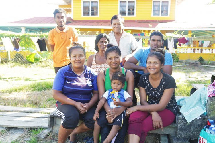 Amina Alberts (centre, forefront) holds her son in her lap. She is surrounded by her relatives.