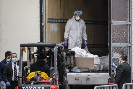 A body wrapped in plastic is loaded onto a refrigerated container truck used as a temporary morgue by medical workers wearing personal protective equipment due to COVID-19 concerns last week at Brooklyn Hospital Center in the Brooklyn borough of New York.