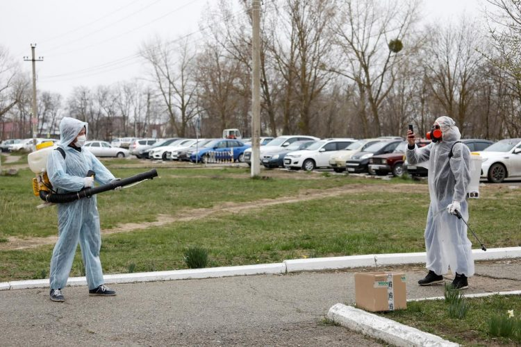 Specialists wearing protective gear take pictures while sanitizing the territory of a local hospital to prevent the spread of the coronavirus disease (COVID-19) in the town of Mikhaylovsk in Stavropol region, Russia April 3, 2020. REUTERS/Eduard Korniyenko