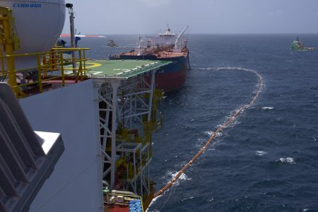 The fuel hose leads from the Liza Destiny FPSO to the Cap Philippe for the transfer of Guyana's first million barrels of crude in February (Ministry of the Presidency photo)