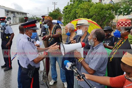David Denny (right) and Lalu Hanuman of The Caribbean Movement for Peace and Integration speaking with police this morning during the protest outside the American Embassy. (Pictures by Reco Moore)