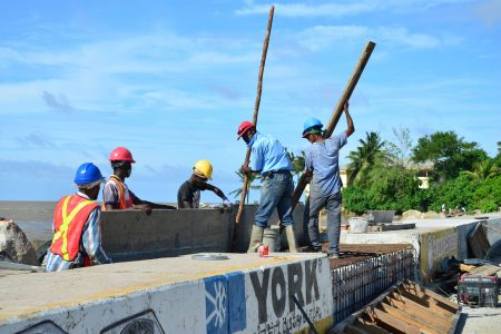 Workers bolstering Kitty sea defence: Rehabilitation works being done on the sea defence in the vicinity of the Kitty Pump Station yesterday. (Orlando Charles photo)