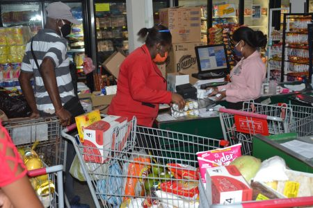 Staff at the Survival Supermarket assisting with checking and packing the trolleys for the beneficiaries. (DPI Photo)
