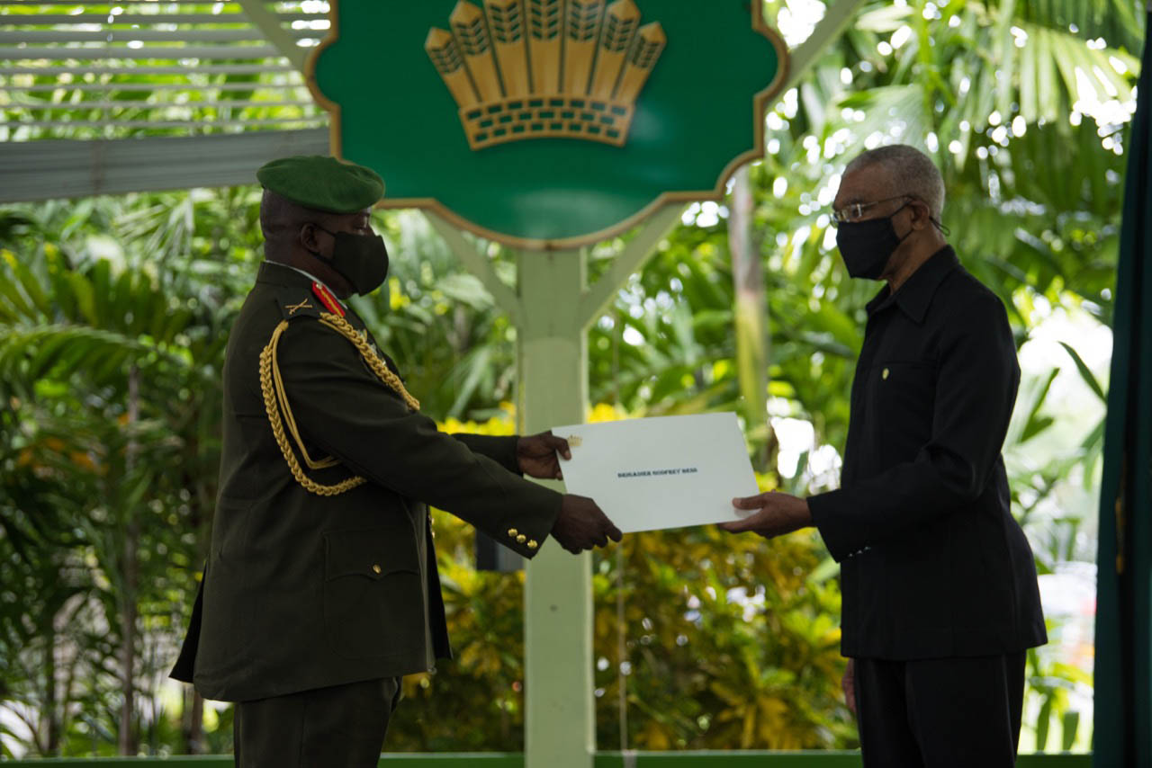 President David Granger presents the Instrument to Brigadier Godfrey Bess, Chief of Staff of the Guyana Defence Force during the Swearing-in Ceremony, yesterday, in the Baridi Benab at State House. (Ministry of the Presidency photo)