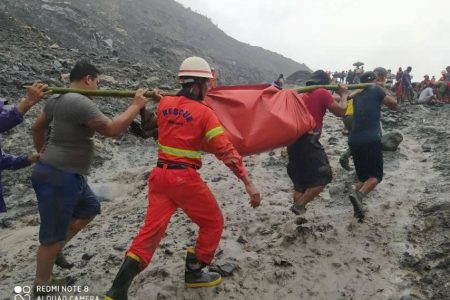 Rescue workers carry a dead body following a landslide at a mining site in Phakant, Kachin State City, Myanmar July 2, 2020, in this picture obtained from social media. MYANMAR FIRE SERVICES DEPARTMENT/via REUTERS