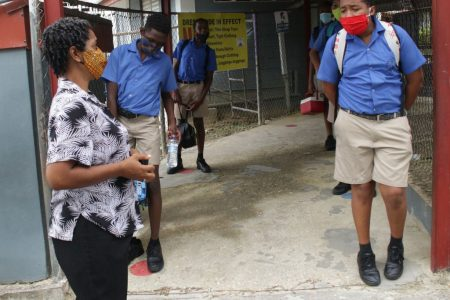 Standard 5 teacher Sharon Jackman chats with her students at the St Paul's Boys' Anglican Primary School, San Fernando, yesterday, after classes were dismissed. Prime Minister Dr Keith Rowley yesterday announced Government had decided to scrap the SEA preparation classes due to the COVID-19 spike.