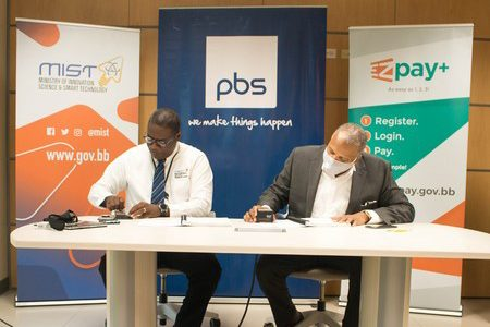 Acting Permanent Secretary in the Ministry of Innovation Science and Smart Technology, Charley Brown (left), and General Manager of Productive Business Solutions (Barbados) Ltd, Elvin Nash, signing the contract to start the Barbados Digital ID and National ID Card Replacement Project. (BGIS)