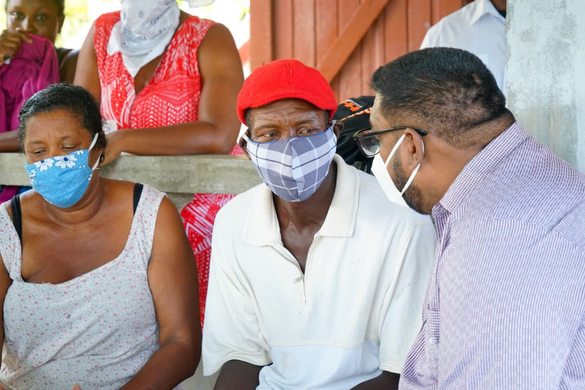 President Irfaan Ali (right) visiting with the family of Isaiah Henry today. (Office of the President photo)