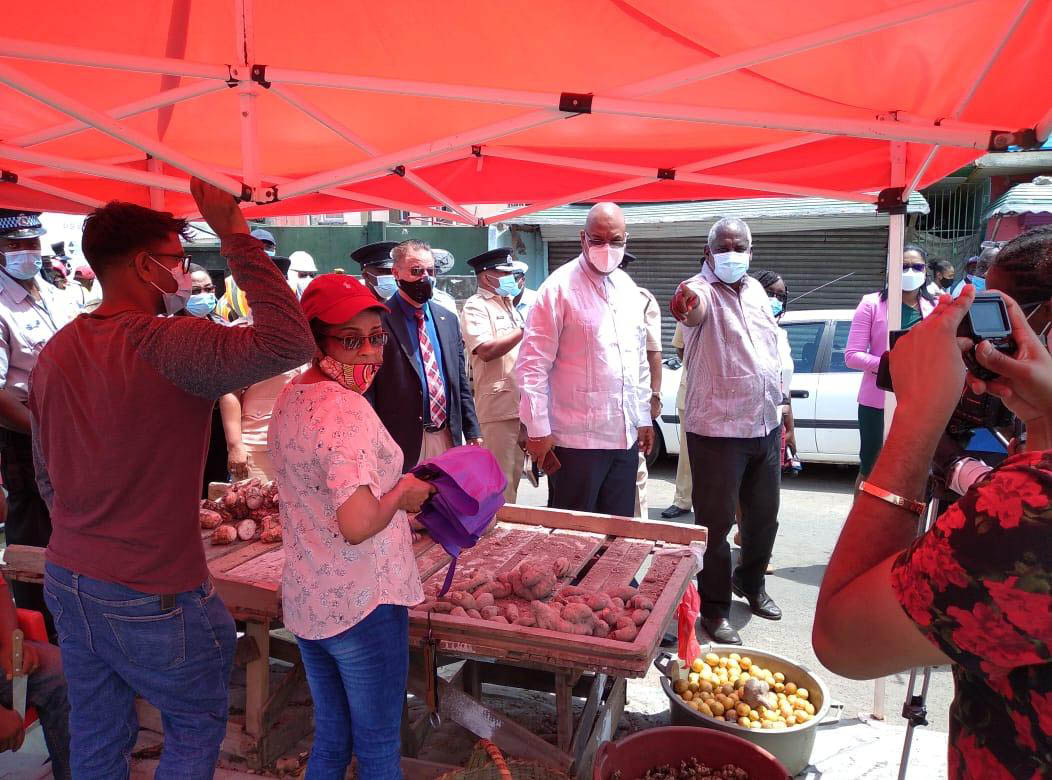 Minister of Home Affairs Robeson Benn (pointing) warns two vendors that they are not supposed to be plying their trade at the location where they currently operate. (Ministry of Public Works photo)