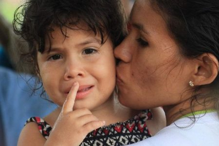 COMFORTED AFTER ORDEAL: Venezuelan mothers comfort their traumatised children on their return to Trinidad yesterday by pirogue after being deported on Sunday.