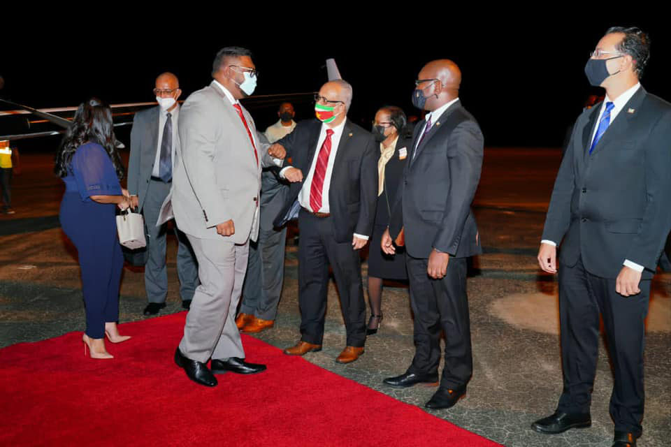 President Irfaan Ali (left) being greeted on his arrival in Suriname last evening by that country's Foreign Minister Albert Ramdin. First Lady Arya Ali is behind the President.