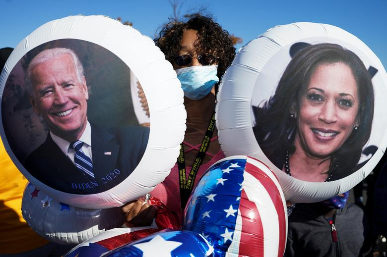 A supporter of Joe Biden holds balloons with the faces of Joe Biden and Kamala Harris as she celebrates near the site of a planned election victory celebration in Wilmington, Delaware, November 7. REUTERS/Kevin Lamarque