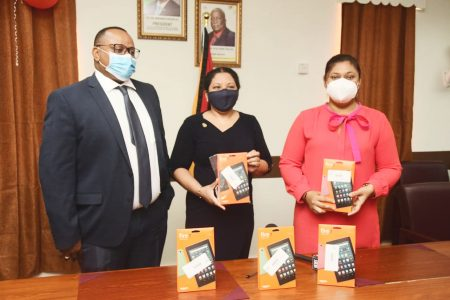 The ANSA McAL Foundation donated 100 Electronic Tablets to the Ministry of Education yesterday. These tablets were purchased with funds raised from the 'ONE YARD' virtual benefit concert which aired on October 30, 2020. From left are Managing Director of ANSA McAL Troy Cadogan, Member of ANSA McAL Foundation Dr. Paloma Mohamed-Martin and Minister of Education Priya Manickchand. (ANSA McAL photo)