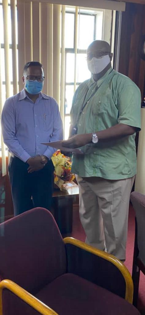 Tameshwar Jagmohan (left) receiving the quarry licence from GGMC Commissioner Newell Dennison