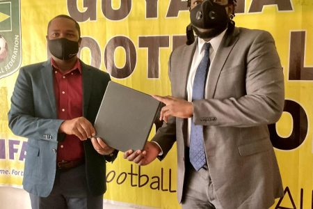 GFF President Wayne Forde (left) handing over the new FIFA approved Disciplinary Code Chairman of the Disciplinary Committee Eusi Anderson.