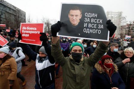 """A participant holds a placard reading """"One for all, all for one"""" during a rally in support of jailed Russian opposition leader Alexei Navalny in Moscow, Russia January 23, 2021. REUTERS/Maxim Shemetov"""