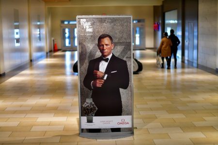 """FILE PHOTO: Shoppers walk past an advertisement for the upcoming James Bond film """"NO TIME TO DIE"""" whose release has been delayed to October, at the Christiana Mall in Newark, Delaware U.S. November 19, 2020. REUTERS/Mark Makela/File Photo"""