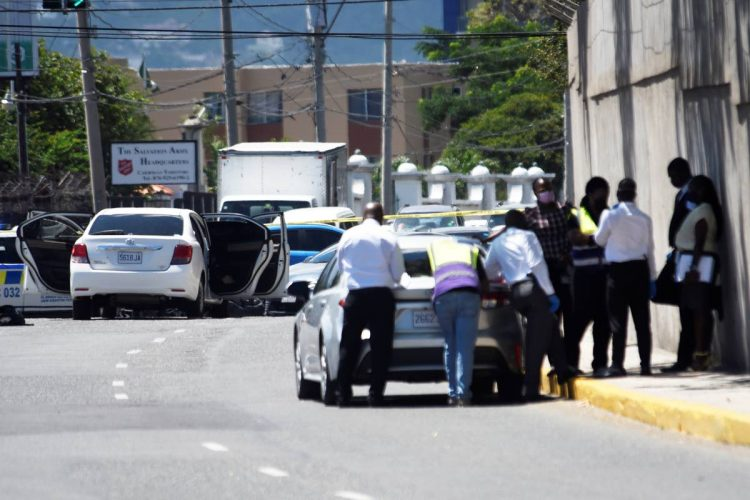 Investigators huddle along Trafalgar Road after police engaged gunmen in a fire fight on Monday. Two men were killed in the incident.