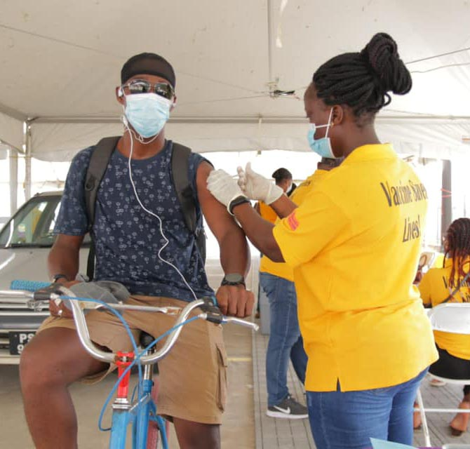 This cyclist took advantage of the Ministry of Health's COVID-19 vaccination drive at MovieTowne yesterday. The event catered for persons getting vaccinated from the comfort of their vehicles. (Department of Public Information photo)