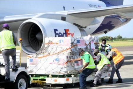 A work crew handles a shipment of 208,000 doses of the Pfizer COVID-19 vaccine, which arrived at the Norman Manley International Airport in Kingston yesterday. The vaccines were donated by the United States.
