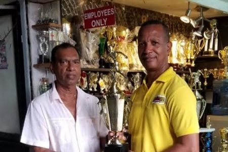 Proprietor of Trophy Stall, Ramesh Sunich (left) hands over a trophy to AAG President AubreyHutsonyesterday.