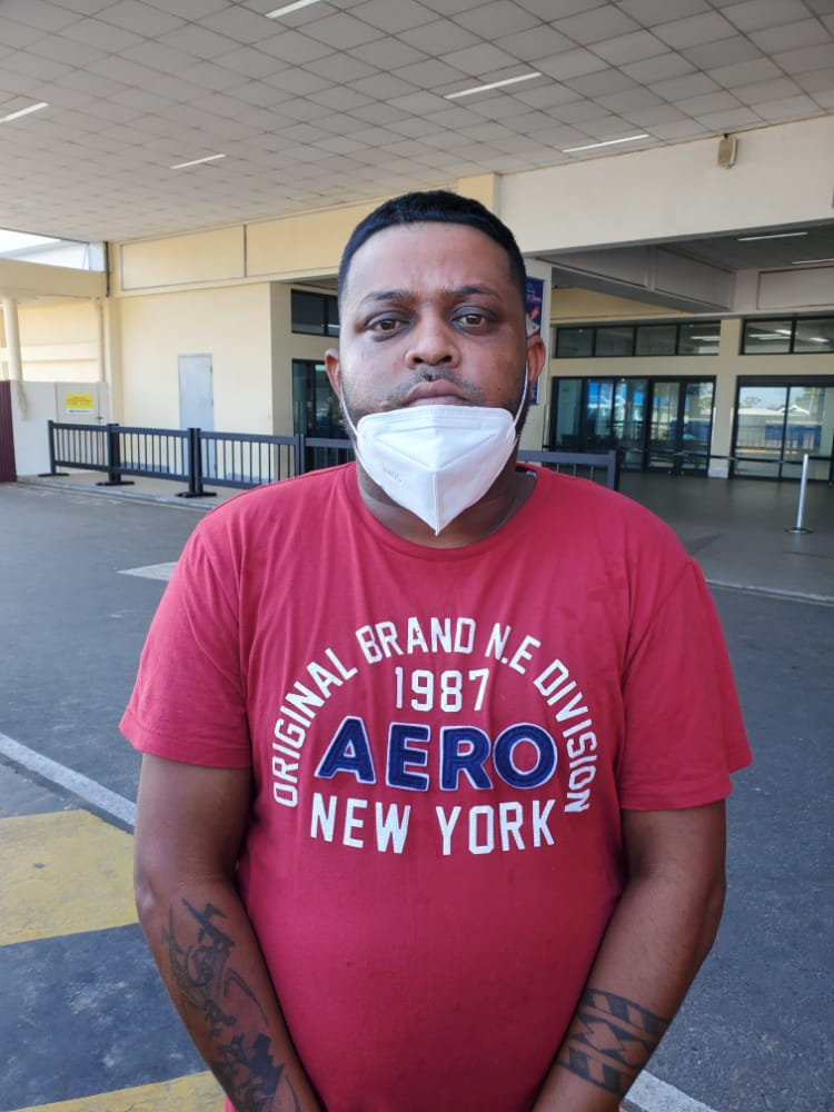 Ganesh Sheocharran at the CJIA this morning after he was returned from JFK in New York [Police photo)