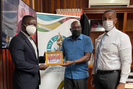After discussing several topics with the top brass of the NSC during a courtesy call, President of the GBBFFI, Keavon Bess (left) presented a signed and framed copy of the CAC team's photo taken in El Salvador.