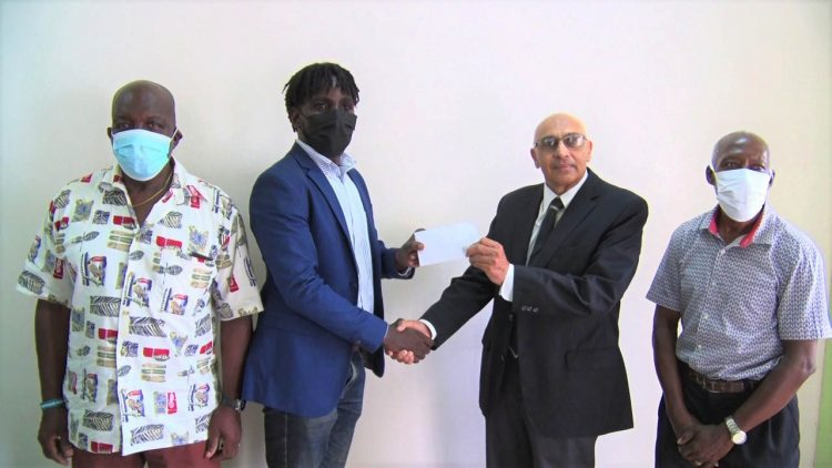 GRFU's Senior Vice-President Joshua Griffith receives the cheque from GOA President K.A Juman-Yassin in the presence of Manager George David (left) and Secretary Terrence Grant.